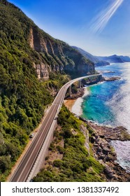 Grand Pacific drive segment of Sea Cliff Bridge passing around steep sandstone cliffs over waves of Pacific ocean on a sunny day in vertical panorama.