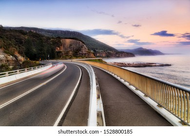 Grand Pacific Drive from Sydney to Wollongong via Sea Cliff Bridge facing north scenic coast of Australian Pacific ocean at sunrise with blurred passing cars.