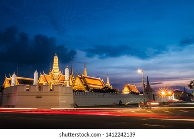 The Grand Palace in Bangkok, Thailand. In the evening, there are lights, cars on the streets and the sky during the twilight.