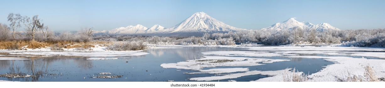 grand panorama of beautiful winter landscape with volcano and lake