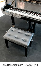 Grand piano with black leather chair on black carpet