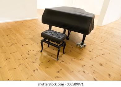 Grand piano and stool in sparse room with white walls and wooden floor