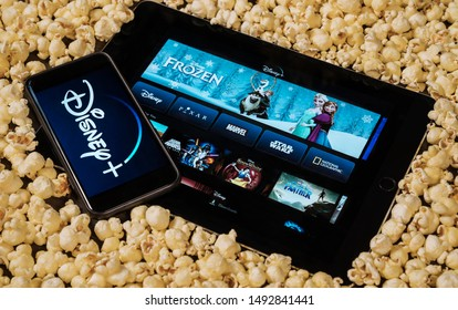 Grand Prairie, TX/USA - AUG 2019: Disney plus on smartphone and iPad/tablet surrounded by popcorn. Disney+ is a new streaming subscription service.