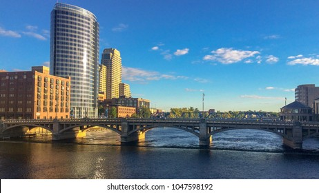 Grand Rapids, MI—Sept 30, 2015 water flows over dam and under bridge at Grand Rapids riverfront on clear fall day.  Grand Rapids is the second largest city in the state of Michigan