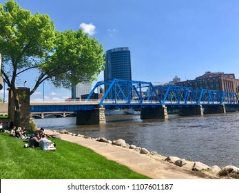 GRAND RAPIDS, MI - May 16, 2018:  People resting on a lawn at the bank of Grand River with a view to Blue Bridge. The bridge was originally constructed as a railroad bridge, later converted to walkway