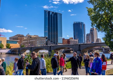 Grand Rapids, MI / USA - 09 29 2018: People stroll along the Grand River with Grand Rapids skyline and Pearl Street bridge in the background.