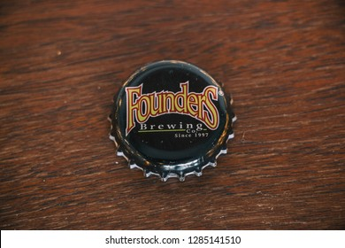 GRAND RAPIDS, MICHIGAN - JAN 14, 2019: Founders Brewing Company beer bottle cap on wood table. American beer based in Grand Rapids, Michigan.