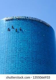 GRAND RAPIDS, MICHIGAN - MARCH 28: Hanging window washers cleaning exterior glass on Helen De Vos Children's Hospital skyscraper city of Grand Rapids, March 28, 2019 in Grand Rapids, Michigan
