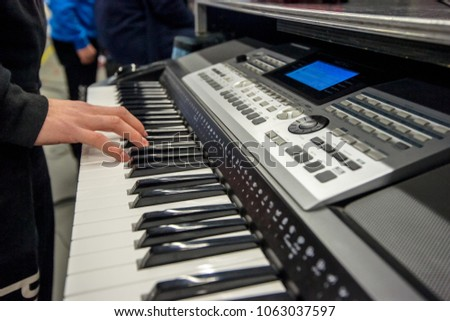 Grand synthesizer or keyboard piano with hands close up that playing the black and white keys