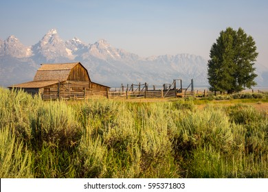 Grand Teton mountain range behind a rustic wooden barn along the famous & historic Mormon Row in Grand Teton National Park,Wyoming