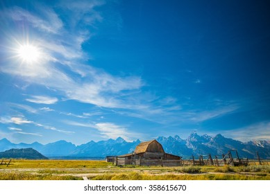 Grand Teton National Park, Jackson Hole, Wyoming.  Barn in a grass field plain against the Grand Teton mountain range with the sun shining