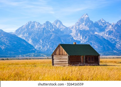 Grand Teton National Park, Wyoming.  Wood Cabin on a Golden Grass Prairie against the Grand Teton Mountains.