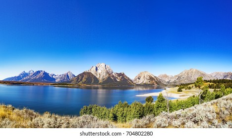 Grand Teton National Park, Wyoming.  Reflection of mountains on Jackson Lake near Yellowstone from island.  Panorama.