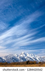 The Grand Teton is seen with whisky clouds above and snow covered peaks just outside of the resort town of Jackson Hole Wyoming