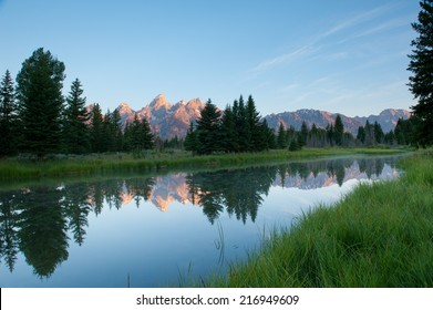 Grand Teton sunrise mountain glow and reflection
