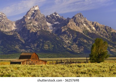 Grand Tetons mountains with barn and fence in foreground