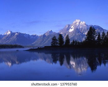 Grand Tetons National Park, Wyoming/ Tetons/Mountain Morgan is reflected in Jackson Lake on a very cool, foggy morning.  All is peaceful.