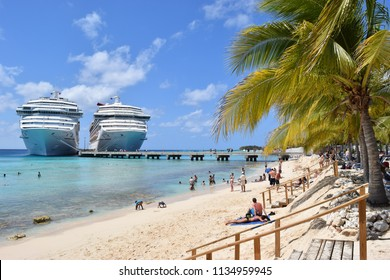 Grand Turk, Turks and Caicos Islands - April 03 2014: Carnival Liberty and Victory Cruise Ships side by side in Grand Turk while passengers relax on a sunny day at Cruise Center (SunRay) Beach.