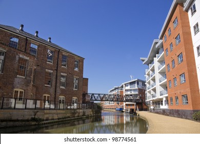 the grand union canal running through old wolverton district of milton keynes in buckinghamshire england, an area of urban regeneration with apartment blocks facing victorian industrial buildings