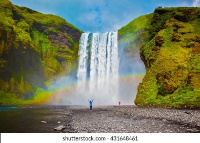 Grand waterfall in Iceland - Skogafoss. Picturesque huge rainbow appears in the water mist. Middle-aged woman - tourist shocked beauty waterfall