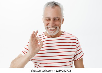 Grandad assuring he not tell parents. Portrait of kind and happy charismatic grandfather in striped t-shirt with white hair and beard winking joyfully showing okay gesture over gray background