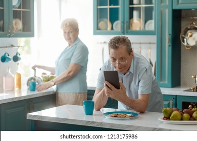 Grandad browsing through web on a cell phone and smiling. Older generation getting tech savvy.