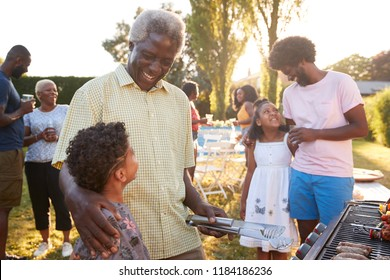 Grandad and dad talking with kids at a family barbecue