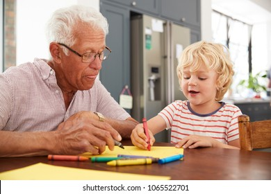 Grandad and grandson drawing together in family kitchen, close up