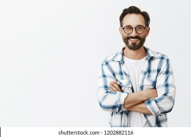 Grandads can be cool, look at me. Portrait of charming and carefree adult man with wrinkles and beard in glasses and clenched shirt, holding hands crossed on chest and smiling broadly at camera