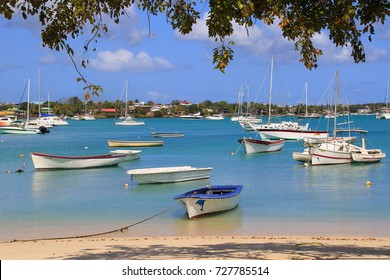 Grand-baie, Mauritius - September 22, 2017: Fishing and pleasure craft moored at the beach in the coastal town in the Riviere du Rempart District on the island