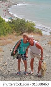 grandchild and grandpa against the background of the sea beach