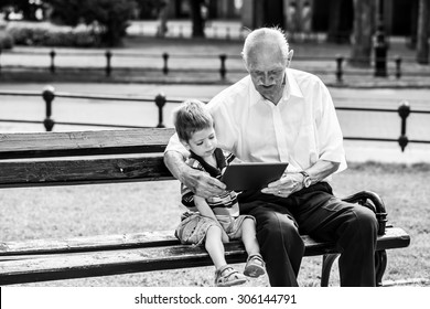 Grandchild teaching to his grandfather to use tablet on a bench. Black and white photography