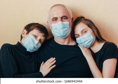Enkelkinder in Gesichtsmasken, die sich auf den Schultern des Großvaters stützten und Angst vor den Folgen der Pandemie hatten. Aufgrund eines plötzlichen Ausbruchs von Coronavirus isoliert. Senior man mit  Selbstisolierung der Kinder