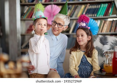 Grandchildren having a good time with their Grandma at a birthday party in a cheerful atmosphere at home. Family, celebration, together