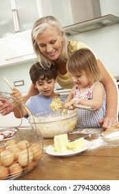 Grandchildren Helping Grandmother To Bake Cakes In Kitchen
