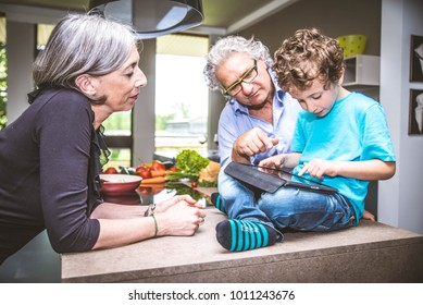 Grandchildren using digital tablet with their grandparents at home