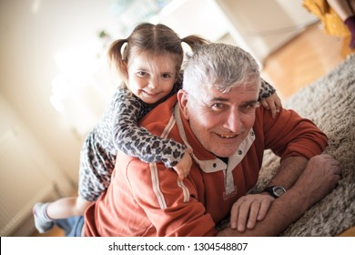 Granddad is always happy to play along. Granddaughter with her grandfather playing at home.