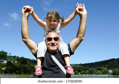 Granddad carry his grandchild on his shoulder during summer vacation.