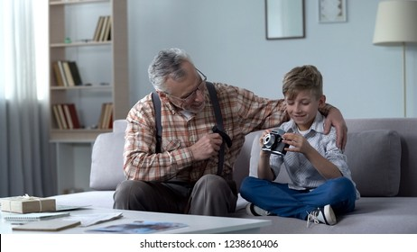 Granddad explaining grandson how to use retro camera, young photographer dreams