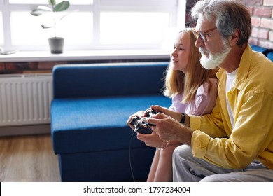 granddad and granddaughter enjoy videogames sit on couch at home, funny relatives playing, looking at pc or tv screen, weekend activity with kids concept