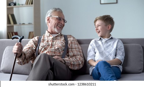 Granddad and grandson laughing genuinely, joking, valuable fun moments together