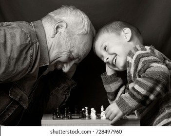 Granddad with grandson on a dark background playing chess