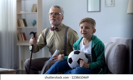 Granddad and grandson watching football together, cheering for favorite team