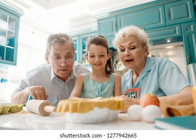 Granddad, granny and granddaughter making a pie together. Family gathered in kitchen, low angle portrait.