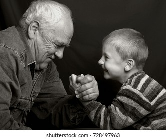 Granddad hand-fighting with grandson on a dark background