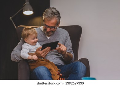 granddad and his grandson sitting on sofa and using tablet