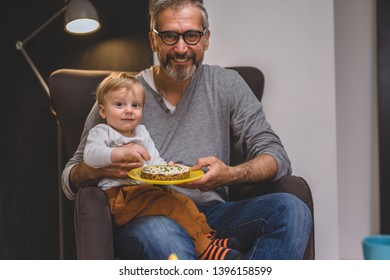 granddad with his grandson sitting sofa and eating sandwich