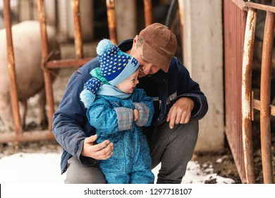Granddad kneeling and making laugh his grandson. Both wearing winter clothes. Winter holiday on the countryside concept.