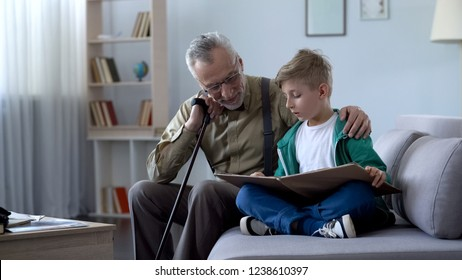 Granddad reading book with boy, doing homework together, upbringing generation
