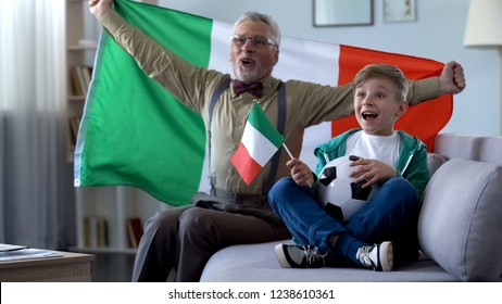 Granddad waving Italian flag, together with boy celebrate victory of soccer team